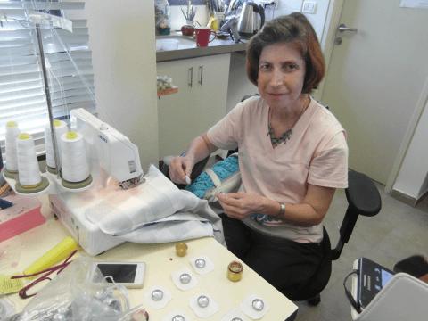 האישה  המיוחדת היוצרת את הכפתורים עוטפת אותם בזהירות ברגישות ובאהבה